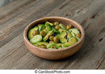 Big bowl of salad with avocado and olives