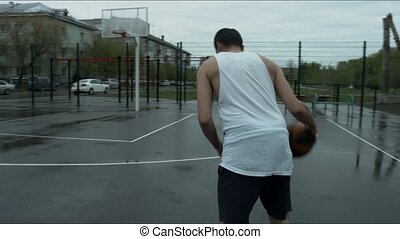 The guy dribbles at basketball court and throws the ball into the ring