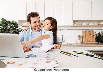 Daughter saying something amusing and pointing at laptop -...