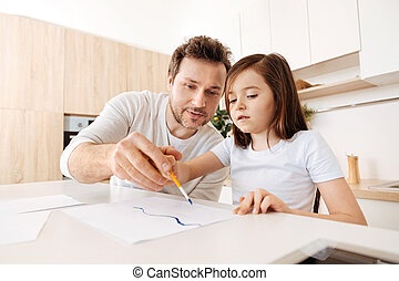 Loving father holding his daughters hand with a brush -...