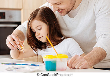 Father gently holding her daughters hand with a brush