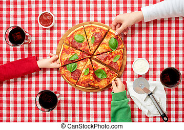 Family in italian national colors clothes taking pieces of pizza, top view