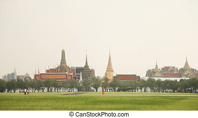 People walk across the field past the Royal Palace. Bangkok,...