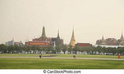 People walk across the field past the Royal Palace. Bangkok,...