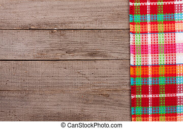Red checkered tablecloth on an old wooden table with copy space for your text. Top view