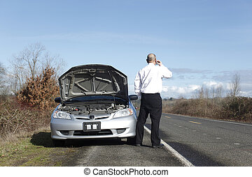 Car trouble - Businessman on cellphone with car trouble.