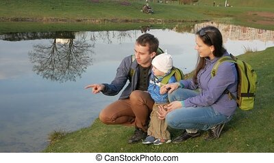 An active young family with a baby sits by the lake in the park and talks to each other