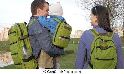 Active family with the baby walks in the park in the spring. Green grass and lake nearby. Green backpacks of different sizes at all
