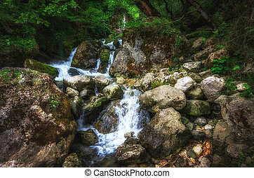 Jungle landscape with flowing turquoise water of georgian cascade waterfall at deep green forest. Mountain of georgia