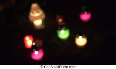 focus change of colourful candle on grave ground in dark. 4K...
