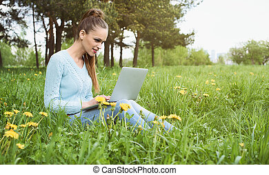young pretty girl working on laptop outdoors, sitting on...