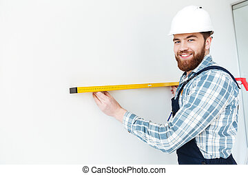 Man holding ruler and looking camera - Young positive man...