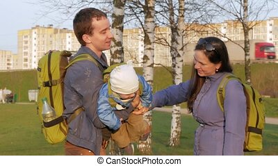 Active family with the baby walks in the park in the spring....
