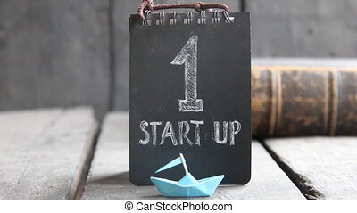 start up success concept, tag, retro book and paper boat -...