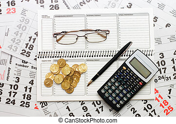 Sheets of a calendar with coins and a notebook