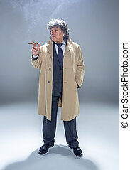 The senior man with cigar as detective or boss of mafia on...