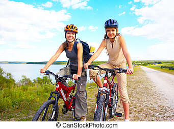Mother and daughter - Mother and a daughter cycling near the...