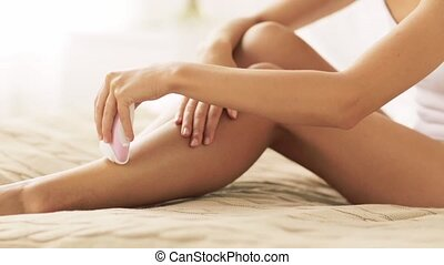 woman with epilator removing hair on legs at home - people,...
