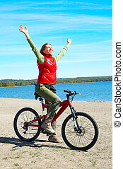 woman - Young smiling  woman cycling near the lake