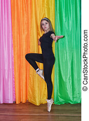 ancer in a black sweat suit, is standing on her toes in a ballet stance