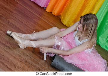 Charming young ballerina puts on Pointe shoes with ribbons -...