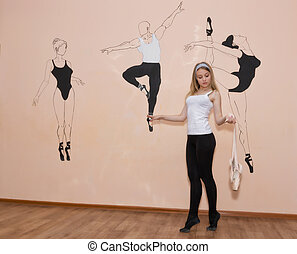 young dancer standing on her toes in a ballet stance with Pointe shoes in hand