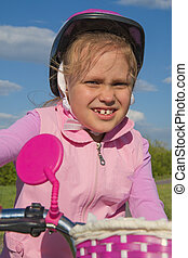 Girl in pink helmet on bicycle, close-up face