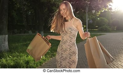 Woman with shopping bags spinning around in park - Excited...