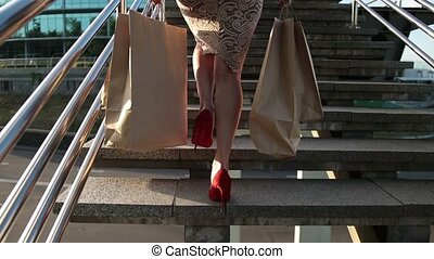 Elegant legs of woman with shopping bags on stairs