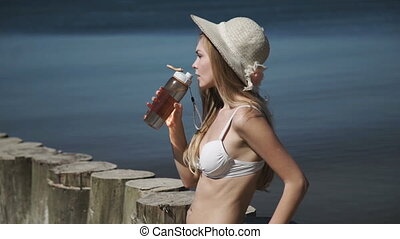 A sexy young woman in a summer hat and a white bikini...