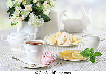 White table with sweets and flowers - Cup of hot tea with...