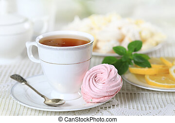 Homemade sweets and lemon - Cup of hot tea with pink...