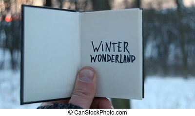 Winter wonderland idea. Book and text. - Hand holding a book...