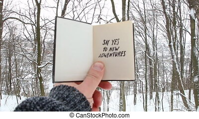 Hand holding a book with the inscription Say yes to new...