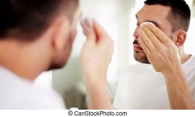 man with cotton pad cleaning face at bathroom - beauty, skin...