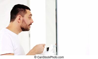 man cleaning ear with cotton swab at bathroom - beauty,...