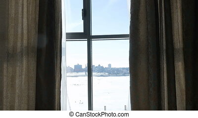 A young, attractive girl in a white coat comes to the window and closes the curtains.