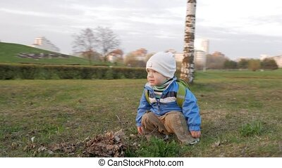 Cute kid is playing in the park with his mother at sunset. He sits, then he gets up. The camera revolves around the boy