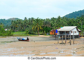 Fishing village with a house on stilts and traditional wooden boat