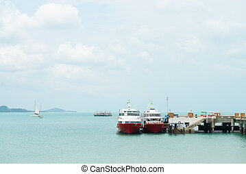 Two boats are at the berth near the pier in clear blue water...