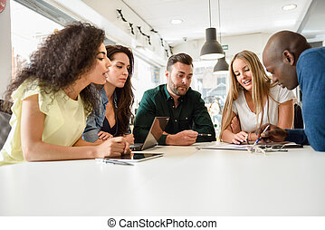 Multi-ethnic group of young people studying together on white desk