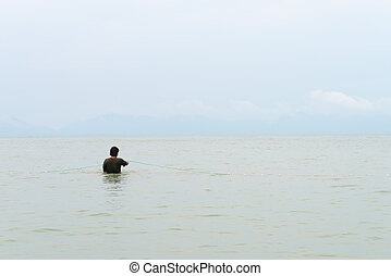 Fisherman in the sea corrects fishing net with view from his...