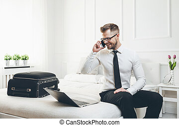 Businessman working from a hotel room with his mobile phone...
