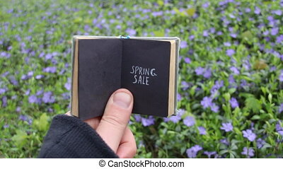 Spring sale idea, book with text and spring field with blue flowers