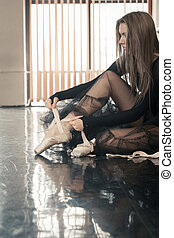 Female ballet dancer puts pointes on - Female ballet dancer...