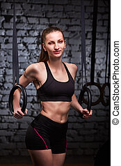 Image of beautiful young sporty woman in the black sportwear doing pull-ups exercise using gymnastic rings.