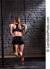 Rear view photo of beautiful young sporty woman in the black sportwear doing pull-ups exercise using gymnastic rings.