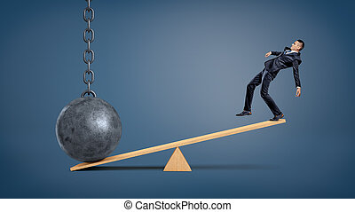 An unbalanced businessman standing on a wooden seesaw and overweighed by a wrecking ball.
