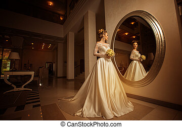 young bride in wedding dress looking at a big mirror -...