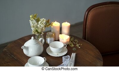 Teapot and cups on a table with flowers and candles